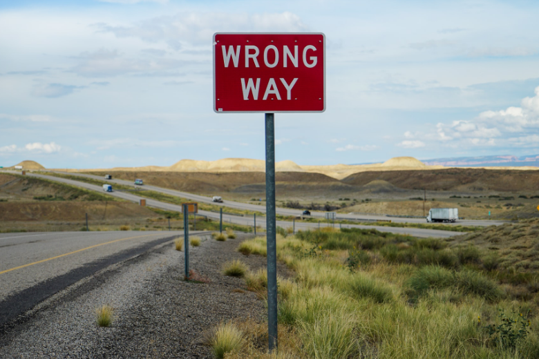 Wrong way sign on the side of a rural highway