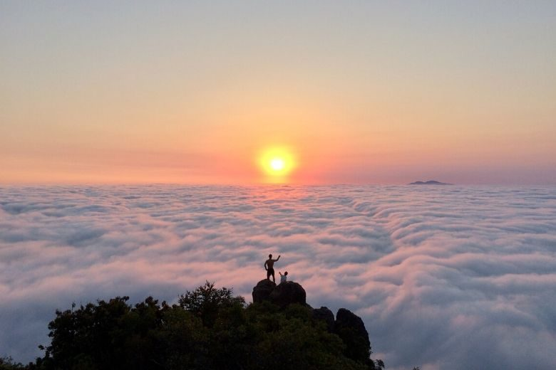 two hikers standing on top of a mountain above the clouds at sunset