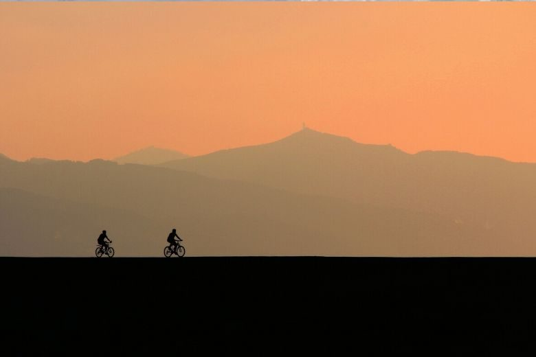 two people riding bikes at sunset