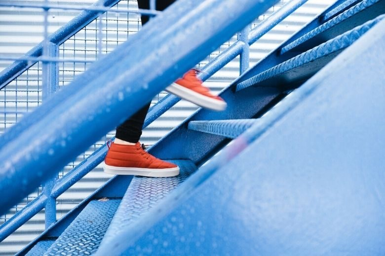 person in red shoes running up blue stairs