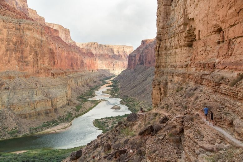 Two hikers hiking along the Colorado River in Grand Canyon National Park
