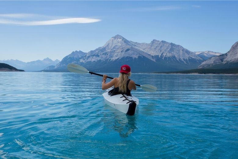 woman kayaking towards the mountains