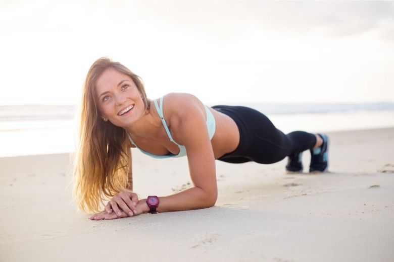 woman smiling while doing a plank on the beach