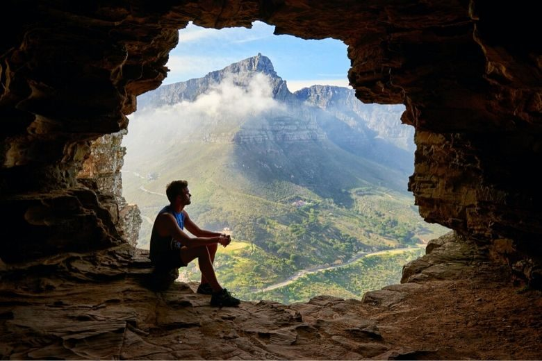 man sitting in a cave and looking thoughtfully out at a mountain