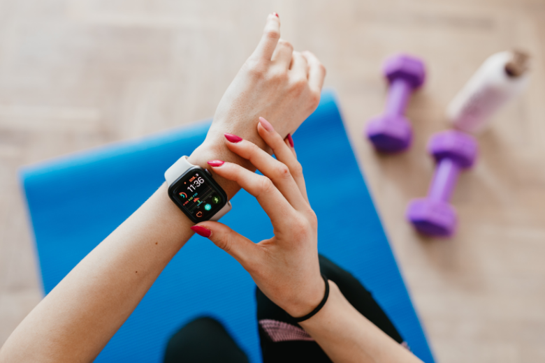 Woman setting fitness tracker watch while sitting on a yoga mat with dumbbells