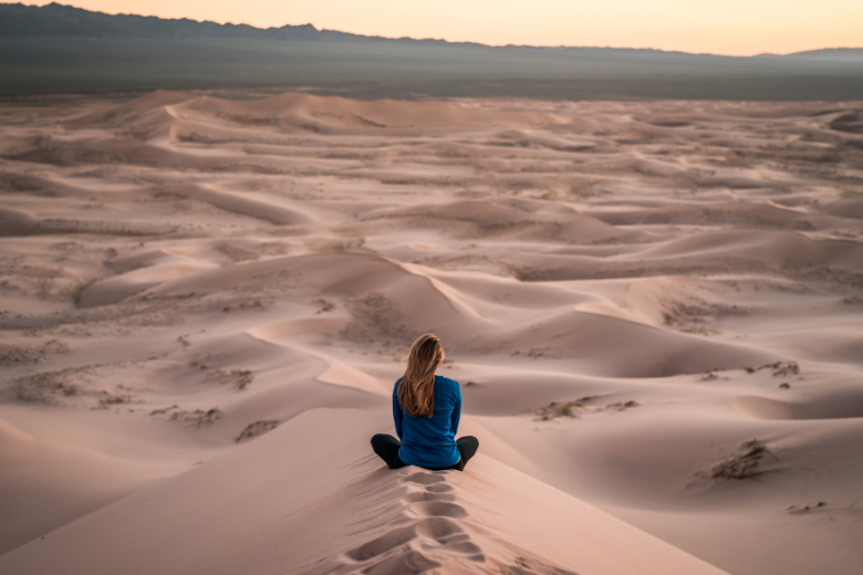 Woman looking out into the desert, thinking.