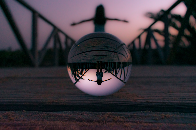 Woman through lensball at sunset